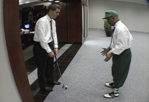 A guy at the Atlanta airport teaches a reporter how to putt